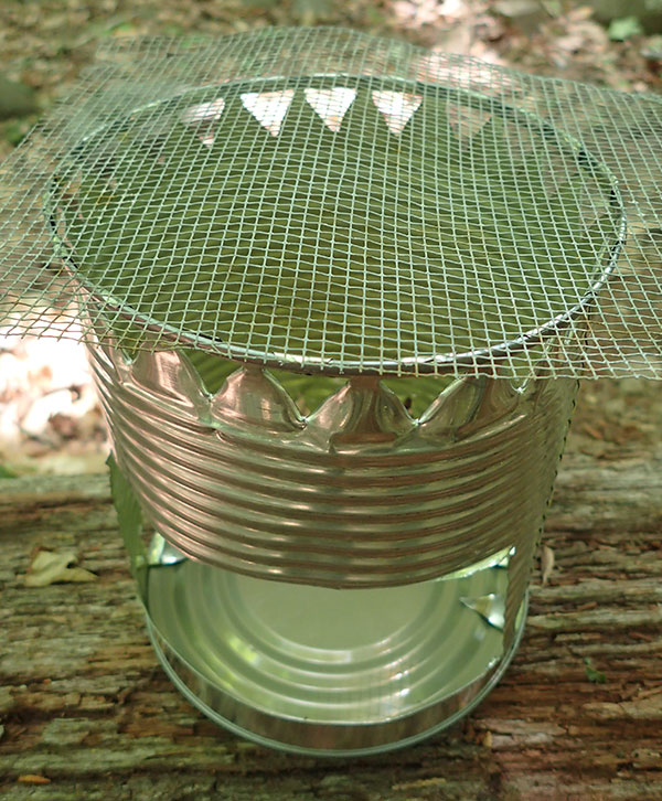 Top of hobo stove was covered with heavy-gauge wire. Metal tent stakes can be used by sliding three or four into vent holes to support item of smaller diameter.
