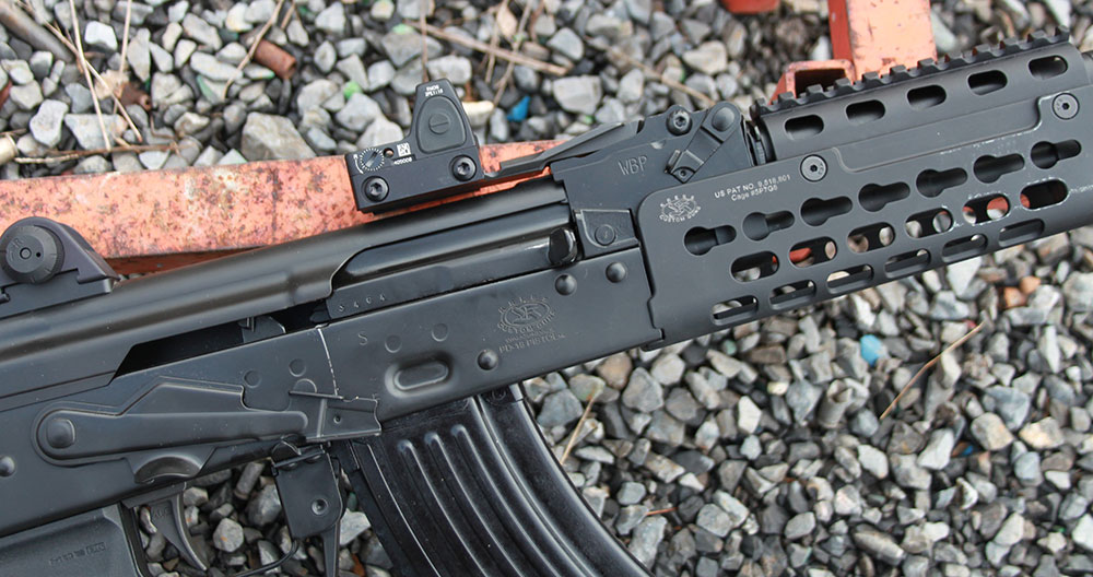 Short rail section anchored at previous rear sight housing protrudes over receiver dust cover and allows for mounting red dot optic.