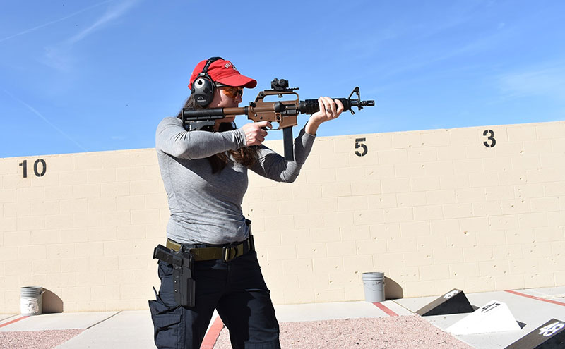 Stacey with carbine and pistol at the range.