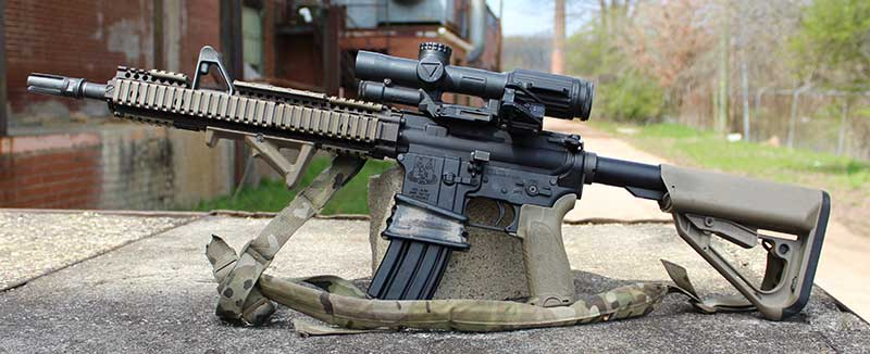 Clone of Gurwitch's last deployment gun outfitted with same buttstock, pistol grip, forearm, sling, SF four-prong flash hider, offset red dot sight, extended mag well, bolt release, and 1-6X variable scope.