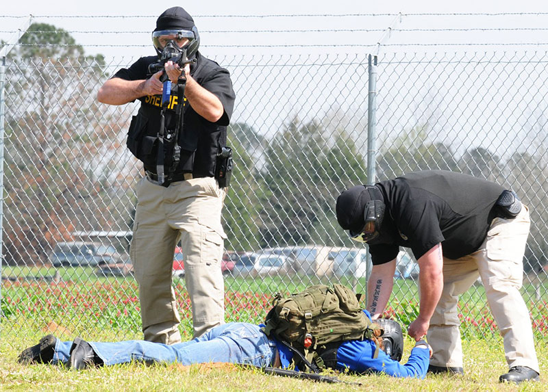 """Members of Coffee County (Alabama) Sheriff's Department apprehend """"suspect"""" during active-shooter exercise conducted at Lucas Stagefield. In active-shooter or terrorist event, EMS won't render aid until scene has been secured. Photo: U.S. Army by Nathan Pfau"""