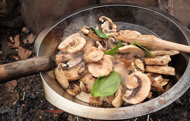 Use an old pie tin for a skillet that can be easily carried or cached in the woods. Stout piece of wood makes a good handle when a notch is cut into it.