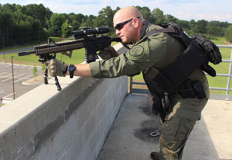 Due to narrow width of ledge, traversing left or right is limited. Even with bipods set on their shortest setting, this officer is still exposed above the wall.