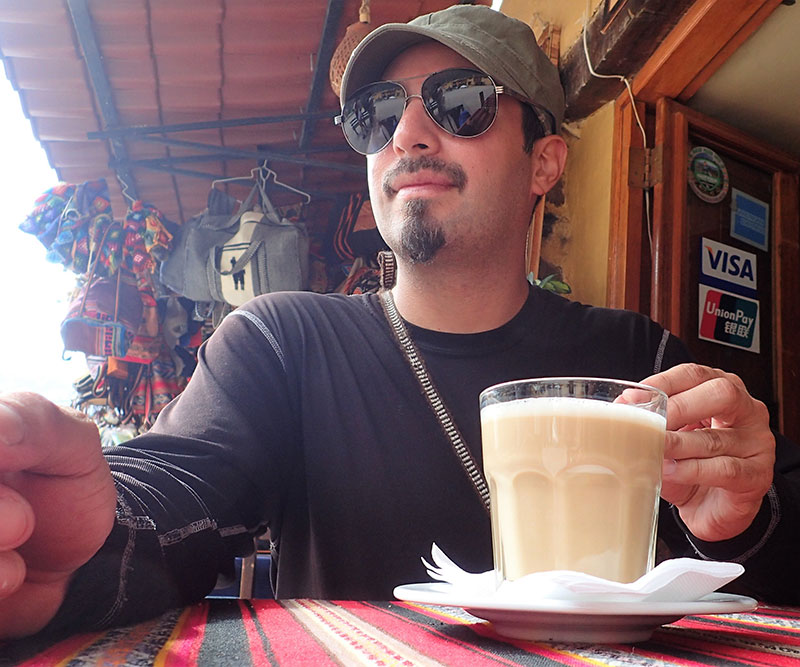 Author in Cusco, Peru, watching LCD screen of his phone to see behind him, with a cup of hot coffee ready for any would-be attacker.