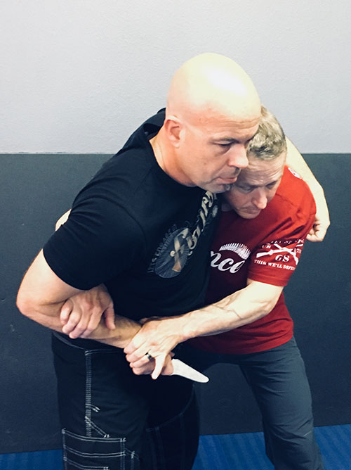 If attacker bends his arm and seizes the defender (a common response), defender steps to attacker's off-side and achieves second point of contact on attacker's weapon-bearing arm. From this position, defender can take attacker to the ground via correctly executed knee bump, or break contact and achieve momentary distance.