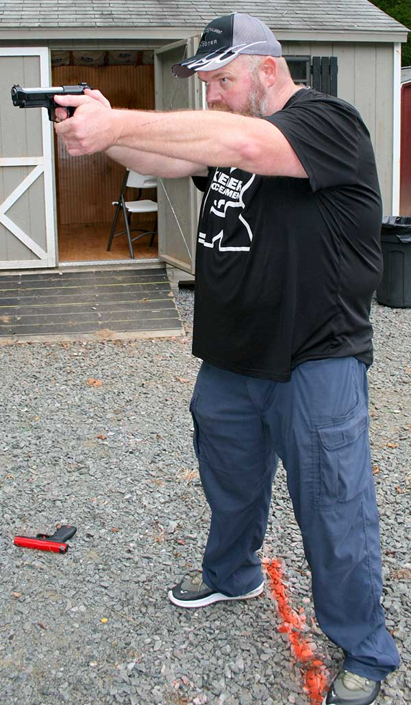 Keepers drives gun straight to the target while prepping his double-action trigger. Arms are fully extended, but elbows are locked and relaxed.
