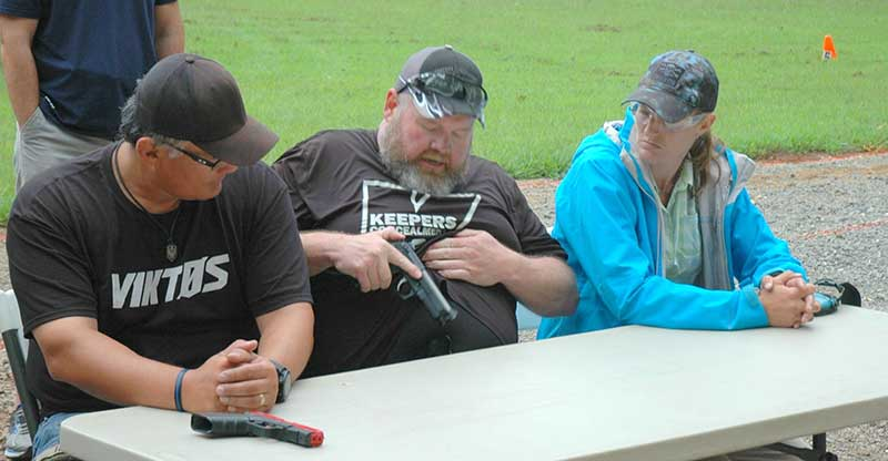 Keepers demos seated draw and holstering. Keepers uses Beretta's hammer as touch point while locking pistol into holster.