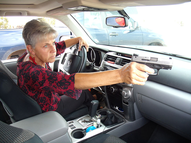 Practicing potential responses to a threat may increase your effectiveness. Author practices addressing a threat through passenger window of her vehicle.