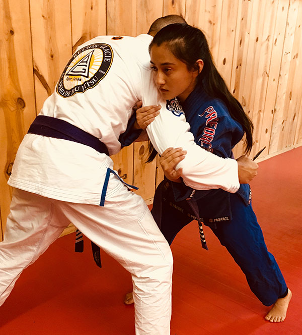 Tala Arthur, Judo Black Belt and Relson Gracie Jiu Jitsu 4-stripe purple belt, works through immediate-action drills with author. Tala has intercepted author's lunge using Red Zone Dive-and-Drive technique prior to establishing two-handed grip known as the Handcuff on his wrist.