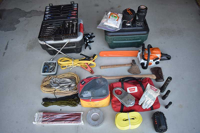 Spare parts, oil, chainsaw, ax, tools, tow strap, stove and food, lights, and winch kit—all secured yet easily accessible.